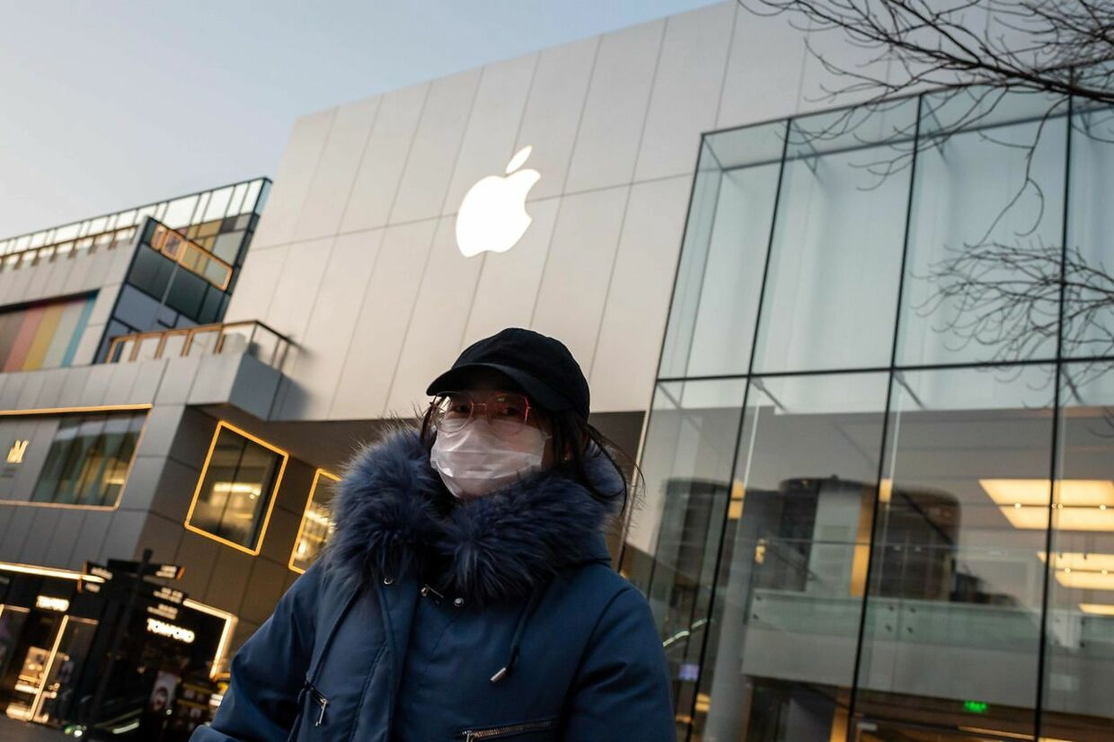 """A woman wearing a protective facemask walks outside of a closed-off Apple Store in Beijing. - Apple shares slid some three percent in opening trade February 18, 2020 after announcing it will take a financial hit from the deadly coronavirus epidemic. The US tech giant said in a statement Monday its revenue for the current quarter would be below its forecasts, and that worldwide iPhone supply """"will be temporarily constrained"""" because of the global virus outbreak, notably in China where Apple manufactures most of its devices."""