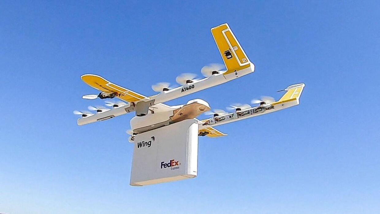 Her ses et billede fra Wing Aviation LLC, der er et andet Alphabet-datterselskab. Der er tale om et af teknologigigantens moonshot-projekter, der i dette tilfælde har specialiseret sig i udviklingen af drone-udbringning. Billedet er fra selskabets pilotprojektaftale om at udføre 'last-mile'-udbringning for pakkemastodonten FedEx samt materialisten Walgreens.